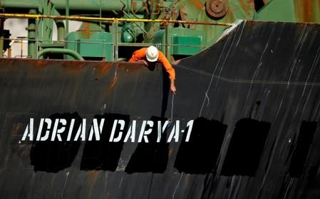 FILE PHOTO: A crew member takes pictures with a mobile phone on Iranian oil tanker Adrian Darya 1, previously named Grace 1, as it sits anchored after the Supreme Court of the British territory lifted its detention order, in the Strait of Gibraltar