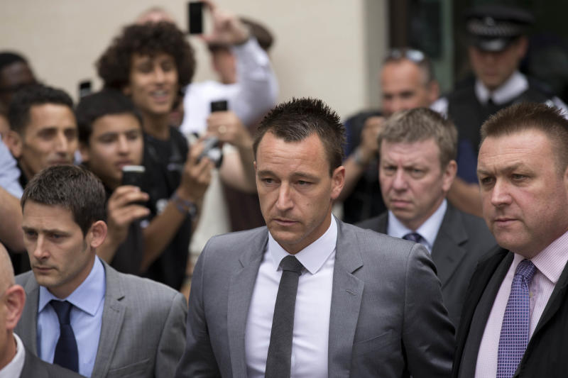 Former England soccer captain and Chelsea player John Terry, center, leaves after being found not guilty at Westminster Magistrates Courts in London, Friday, July 13, 2012. Chelsea captain John Terry was cleared Friday of racially abusing an opponent, Queens Park Rangers player Anton Ferdinand, during a Premier League match after one of the most high-profile trials involving a soccer player. The case led to Terry being stripped of the England captaincy by the Football Association ahead of the European Championship and the departure of coach Fabio Capello who disagreed with the decision. (AP Photo/Matt Dunham)