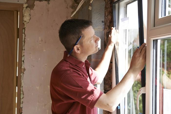 A contractor installs a new window.