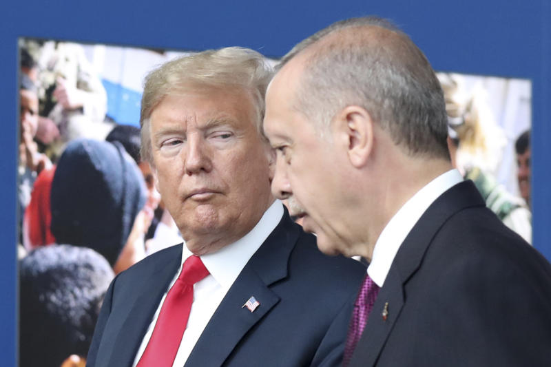 FILE - In this July 11, 2018 file photo, President Donald Trump, left, talks to Turkish President Recep Tayyip Erdogan as they tour the new NATO headquarters in Brussels, Belgium. Trump's decision to withdraw American troops from Syria was made hastily, without consulting his national security team or allies, and over the strong objections of virtually everyone involved in the fight against the Islamic State, according to U.S. officials. Trump stunned his Cabinet, lawmakers and much of the world with the move that triggered Defense Secretary Jim Mattis' resignation by rejecting the advice of his top aides and agreeing to the pull-out in a phone call with Turkish President Recep Tayyip Erdogan last week, two officials briefed on the matter said. (Tatyana Zenkovich/pool photo via AP)