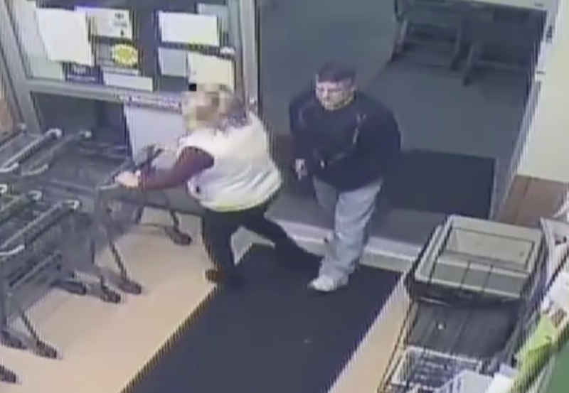 A Maryland shopper pulls out a trolley before she is stabbed by what is believed to be a syringe by a man who is standing behind her in a black jumper.
