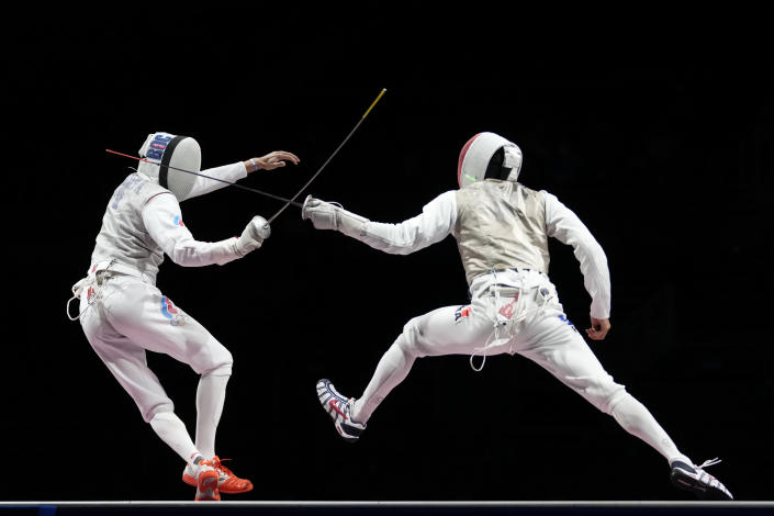 Anton Borodachev of the Russian Olympic Committee, left, and Erwann Le Pechoux of France compete in the men's Foil team final at the 2020 Summer Olympics, Sunday, Aug. 1, 2021, in Chiba, Japan. (AP Photo/Andrew Medichini)