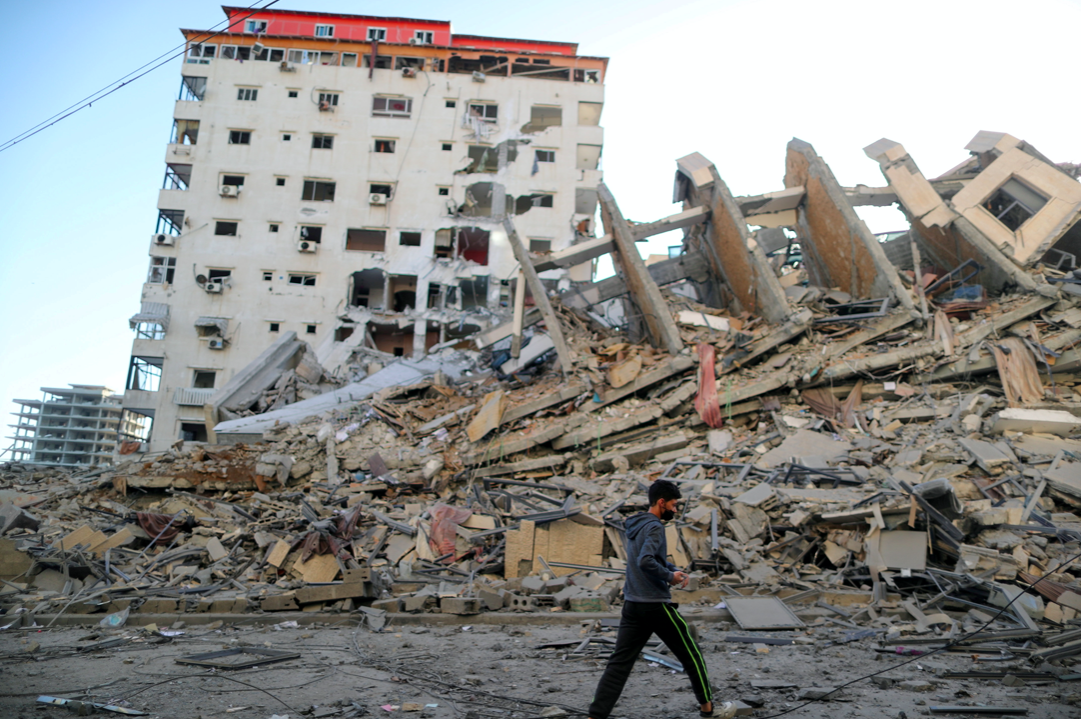 A Palestinian boy walks past the remains of a tower building which was destroyed in Israeli air strikes, in Gaza City. (Reuters/Suhaib Salem)