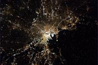"""Boston at night, glowing under a trace of fog. <a href=""""https://twitter.com/Cmdr_Hadfield/"""" rel=""""nofollow noopener"""" target=""""_blank"""" data-ylk=""""slk:(Photo by Chris Hadfield/Twitter)"""" class=""""link rapid-noclick-resp"""">(Photo by Chris Hadfield/Twitter)</a>"""
