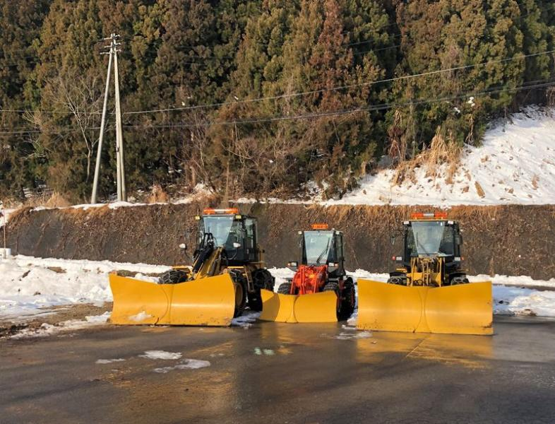 Snow ploughs are parked near a snow resort in Iiyama
