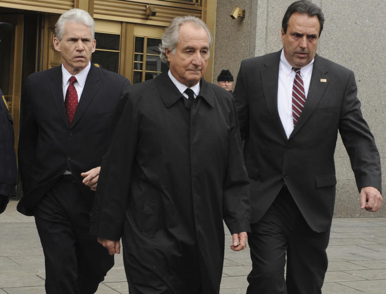 FILE - In this March 10, 2009 file photo, Bernard Madoff, center, exits Manhattan federal court in New York. Madoff, who pleaded guilty in 2009 to orchestrating the largest Ponzi scheme in history, is seeking an early release from prison. The Department of Justice confirmed on Wednesday, July 24, 2019 that Madoff has a pending request to get his 150-year sentence reduced. (AP Photo/Louis Lanzano, file)