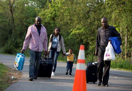 A family that said they are from Haiti walks to the US-Canada border from Roxham Road in Champlain, New York, U.S. August 11, 2017. REUTERS/Christinne Muschi