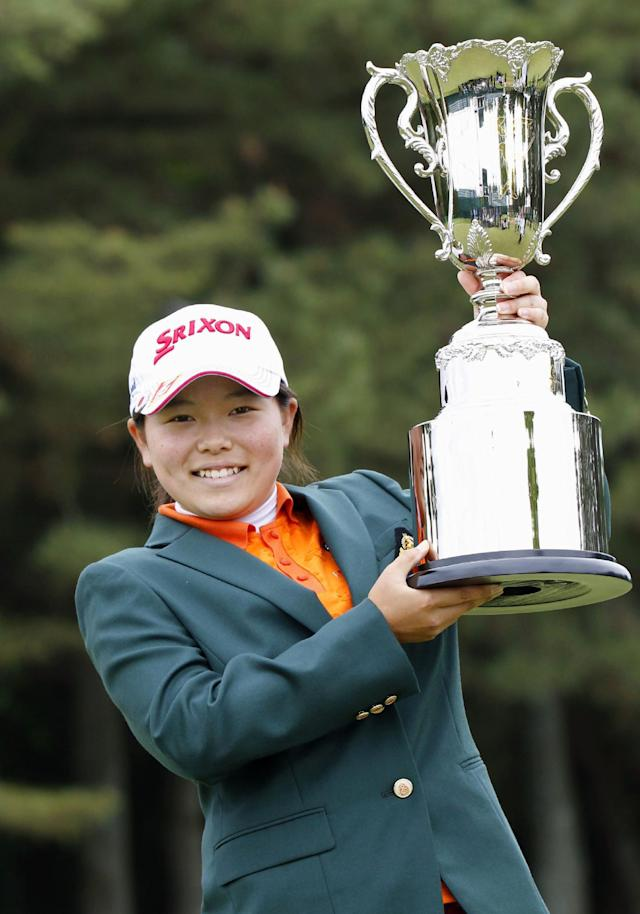 Minami Katsu poses with her trophy after winning the Vantelin Ladies Open golf tournament at Kumamoto Airport Country Club in Kumamoto, southwestern Japan, Sunday, April 20, 2014. Katsu, a 15-year-old Japanese high school student, became the youngest winner in the history of the Japan LPGA tour by shooting a 4-under 68 in the tournament. (AP Photo/Kyodo News)