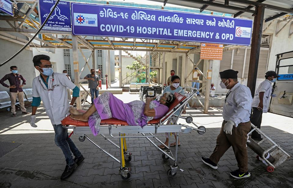 Indian health workers bring a suspected Covid-19 positive patient into a hospital in Ahmedabad, India (EPA)
