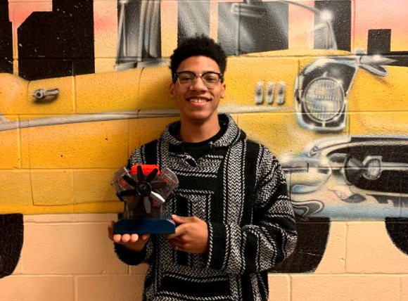 Akron student Kyrice Brunson shows off one of the engine models automotive students in the district built during the pandemic, instead of taking apart and rebuilding a real engine at school. (Courtesy of Akron Public Schools)