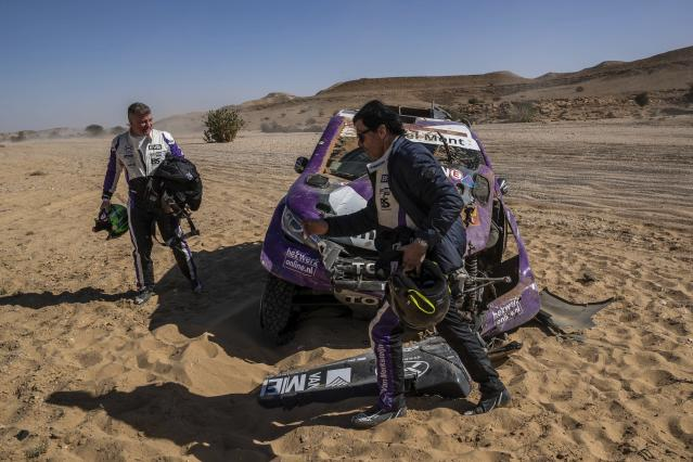 In this Tuesday, Jan. 14, 2020 photo, driver Peter Van Merksteijn, of Netherlands, foreground, and co-driver Michael Orr, of Great Britain, after crashing their Toyota during stage nine of the Dakar Rally between Wadi Al Dawasir and Haradth, Saudi Arabia. Formerly known as the Paris-Dakar Rally, the race was created by Thierry Sabine after he got lost in the Libyan desert in 1977. Until 2008, the rallies raced across Africa, but threats in Mauritania led organizers to cancel that year's event and move it to South America. It has now shifted to Saudi Arabia. The race started on Jan. 5 with 560 drivers and co-drivers, some on motorbikes, others in cars or in trucks. Only 41 are taking part in the Original category. (AP Photo/Bernat Armangue)