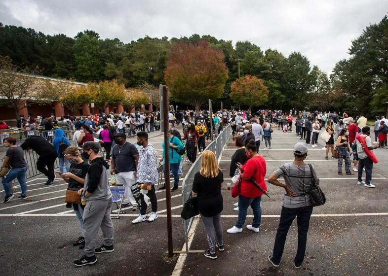 Hundreds of people wait in line for early voting in Marietta, Georgia, Monday, Oct. 12, 2020. (AP Photo/Ron Harris, File)