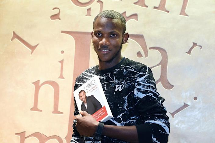 Lassana Bathily, the employee of the Hyper Cacher jewish supermarket in Paris who helped shoppers hide from an islamist gunman who attacked the store on January 9, 2015, poses with book 'Je ne suis pas un heros' ('I Am Not A Hero') (AFP Photo/Dominique Faget)