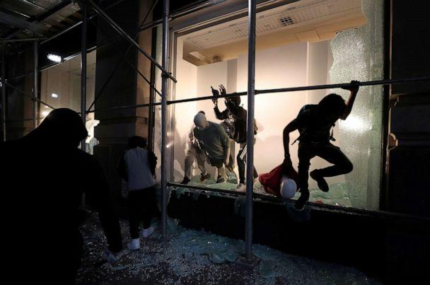 PHOTO: A man jumps from the window of a damaged store in New York City, June 2, 2020. (Jeenah Moon/Reuters)