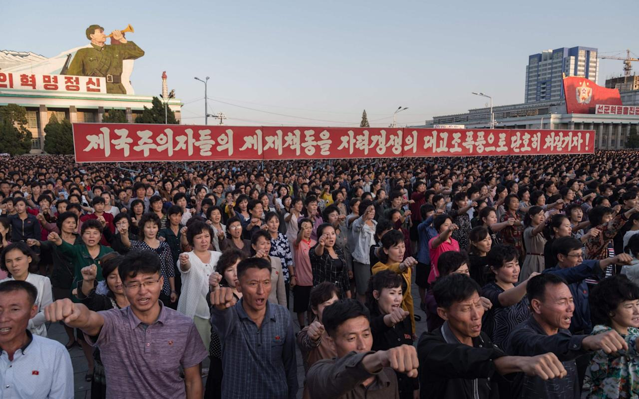 """Tens of thousands of Pyongyang residents were gathered in the capital's Kim Il-Sung Square Saturday to laud leader Kim Jong-un's denunciation of US President Donald Trump. Such set-piece rallies, organised by the authorities, are a regular feature of political life in Pyongyang, and are intended as a physical demonstration of popular support for the leadership. Students in white shirts and red ties held up the red flag of the ruling Workers' Party, with a yellow ink brush representing intellectuals, a hammer for the workers, and a sickle for the peasantry. Ranks of workers and residents listened, their fists clenched, as speakers repeated Mr Kim's denigration of Mr Trump as """"mentally deranged"""" and a """"dotard"""". The US president dubbed Mr Kim """"Rocket Man"""" in a speech at the United Nations last week in which he threatened to """"totally destroy"""" the North if it attacked the US or its allies. Students march during a mass rally on Kim Il-Sung sqaure in Pyongyang on September 23, 2017 Credit: KIM WON-JIN/AFP In a statement on Friday Mr Kim responded by saying that """"a frightened dog barks louder"""" and Trump would """"pay dearly"""" for his comments - triggering the US head of state to describe him as a """"madman"""". On one side of the square a giant poster depicted innumerable red missiles plunging towards a collapsing US Capitol, with the slogan """"Korea's Answer"""". The bellicose rhetoric between Mr Kim and Mr Trump has become increasingly personal, and raised fears of miscalculation in the standoff over the North's nuclear weapons and ballistic missiles. Students march during a mass rally on Kim Il-Sung sqaure in Pyongyang on September 23, 2017 Credit: KIM WON-JIN/AFP """"I would like to put down my pen and take up arms again to perform my duty to defend the fatherland,"""" said Pyongyang Mechanical University student Ri Il Ung, 24. """"Trump is a warmonger and a backstreet gangster,"""" he added. """"It's quite ridiculous that such a person could become a politician."""" Ordinary North Koreans normally on"""