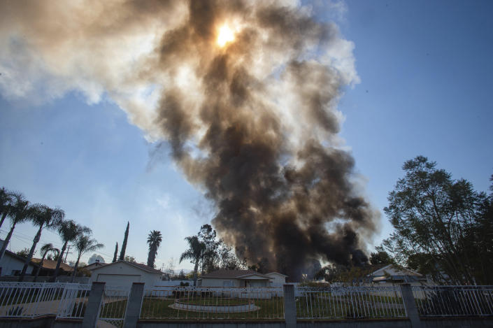 Smoke rises in the background after a fireworks stash exploded in Ontario, Calif., Tuesday, March 16, 2021. (Watchara Phomicinda/The Orange County Register via AP)