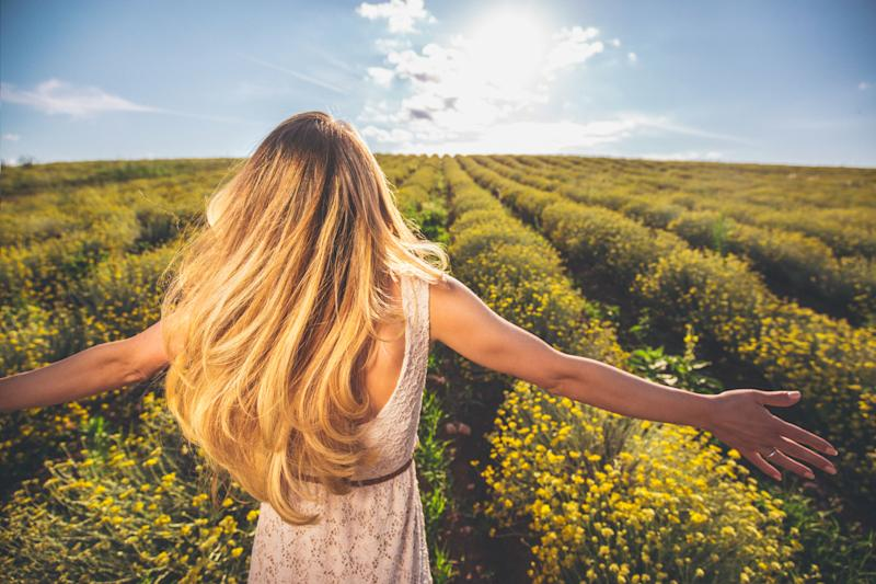 Photo of a young woman with arms outstretched walking down the immortelle flower field, enjoying life