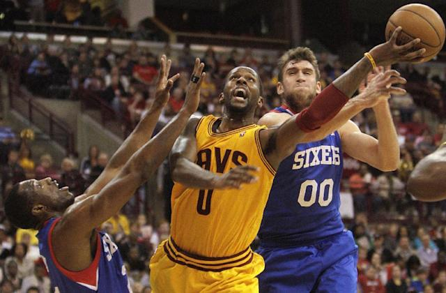 Cleveland Cavaliers' C.J. Miles, center, takes a shot between Philadelphia 76ers' Thaddeus Young, left, and Spencer Hawes during the third quarter of an NBA preseason basketball game Monday, Oct. 21, 2013, in Columbus, Ohio. The Cavaliers beat the 76ers 104-93. (AP Photo/Jay LaPrete)