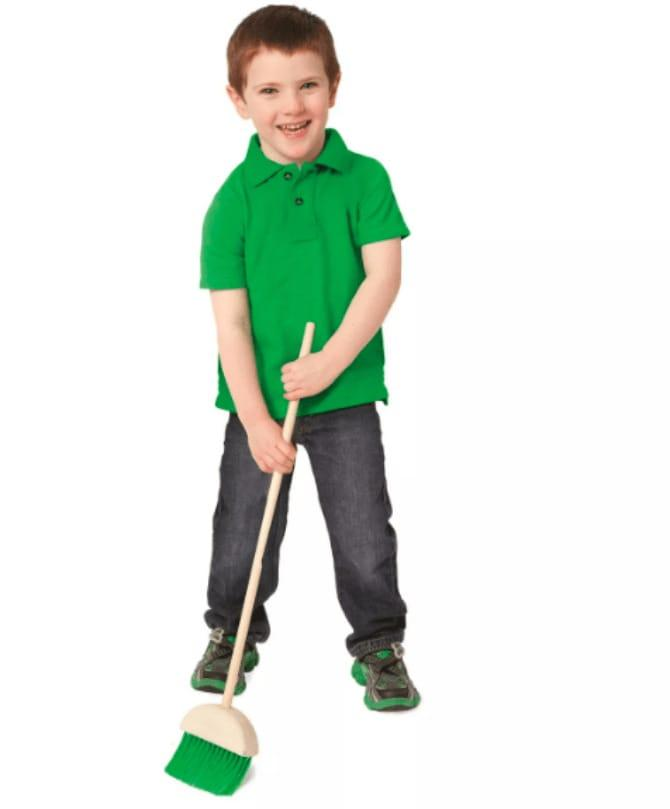 Boy in green t shirt with green broom