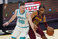 Cleveland Cavaliers' Isaac Okoro (35) drives past Charlotte Hornets' Gordon Hayward (20) during the first half of an NBA basketball game Wednesday, Dec. 23, 2020, in Cleveland. (AP Photo/Tony Dejak)