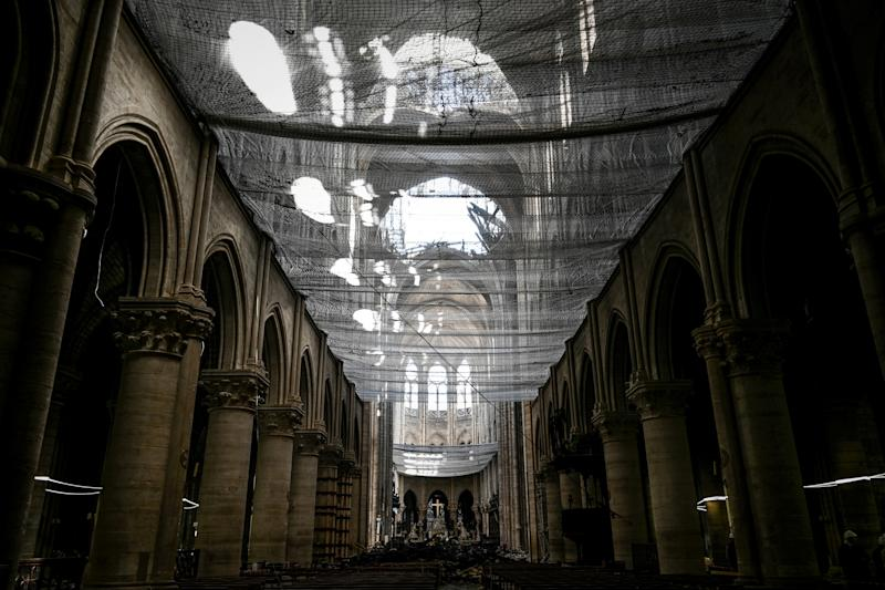 A picture shows a protective net inside the Notre-Dame Cathedral during the preliminary work in the Notre-Dame Cathedral one month after it sustained major fire damage in Paris