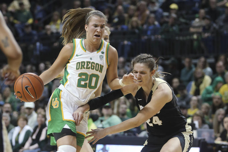 Oregon's Sabrina Ionescu, left, drives to the basket as Colorado's Aubrey Knight defends during the second quarter of an NCAA college basketball game in Eugene, Ore., Friday, Jan. 3, 2020. (AP Photo/Chris Pietsch)