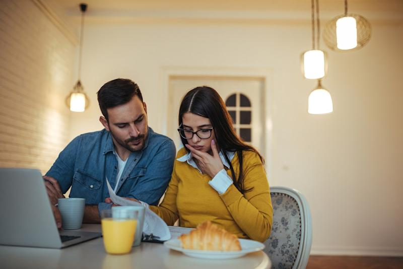 couple eating breakfast looking at laptop and papers concerned