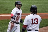 Boston Red Sox's Dustin Pedroia, left, is congratulated by teammate Hanley Ramirez after scoring on a double by designated hitter David Ortiz against the Minnesota Twins during the first inning in the first baseball game of a doubleheader at Fenway Park in Boston, Wednesday, June 3, 2015. (AP Photo/Charles Krupa)