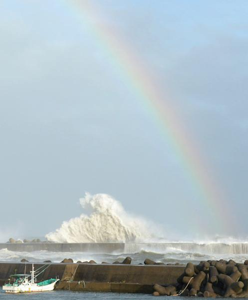 A rainbow appears while high waves hit a breakwater in Kihocho, Mie prefecture, western Japan Sunday, Sept. 30, 2012. A powerful typhoon is heading to Tokyo after injuring dozens of people, causing blackouts and paralyzing traffic in southern Japan. (AP Photo/Kyodo News) JAPAN OUT, MANDATORY CREDIT, NO LICENSING IN CHINA, FRANCE, HONG KONG, JAPAN AND SOUTH KOREA