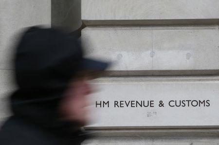 FILE PHOTO: A pedestrian walks past the headquarters of Her Majesty's Revenue and Customs (HMRC) in central London, Britain February 13, 2015.  REUTERS/Stefan Wermuth/File Photo
