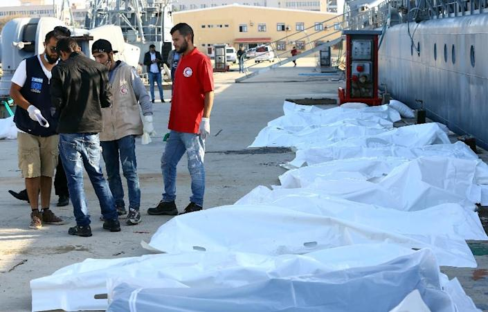 Libyan paramedics and aid workers stand next to the bodies of African migrants at a naval base in Tripoli on November 25, 2017, after more than 30 migrants died off the coast of Garabulli, 60 kilometres (40 miles) east of the capital (AFP Photo/MAHMUD TURKIA)