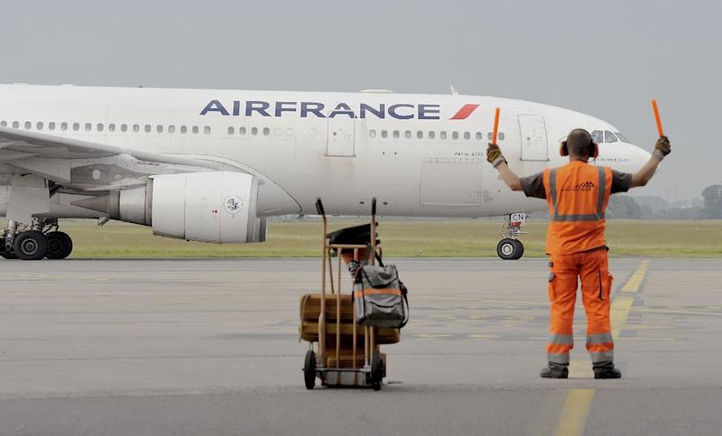 A runway agent guides an Air France airliner on June 9, 2014 at Lille's airport