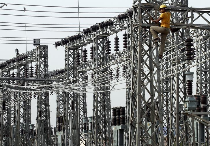 An employee works on electric pylons at a power station in Greater Noida