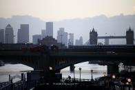 Canary Wharf can be seen in the distance as a person walks along a footbridge, amid the coronavirus disease (COVID-19) outbreak, in London