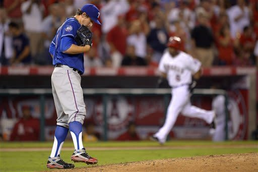 Texas Rangers starting pitcher Derek Holland, left, kicks at the dirt as Los Angeles Angels' Alberto Callaspo rounds third after hitting a two-run home run during the fifth inning of their baseball game, Wednesday, Sept. 19, 2012, in Anaheim, Calif. (AP Photo/Mark J. Terrill)