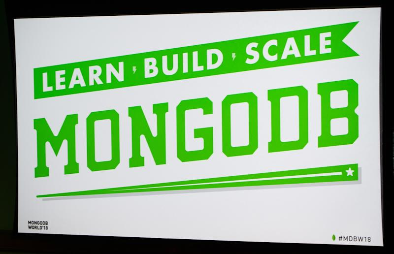 Green and white promo board with MongoDB logo and slogan on it.
