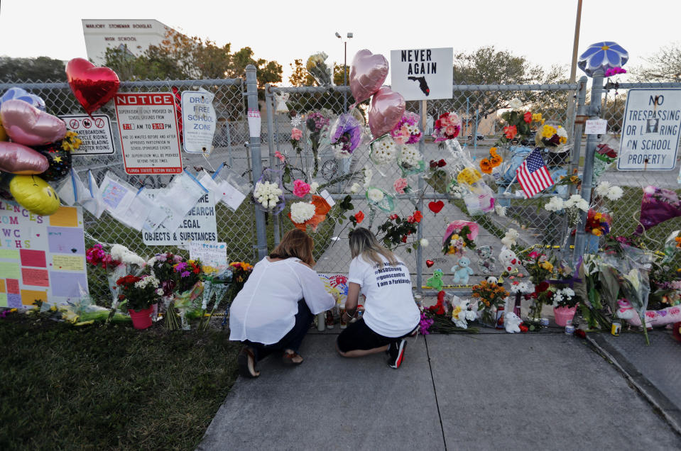 FILE - In this Feb. 18, 2018 file photo, people light candles at a makeshift memorial outside Marjory Stoneman Douglas High School, where 17 students and faculty were killed in a mass shooting days earlier in Parkland, Fla. Sorrow is reverberating across the country Sunday, Feb. 14, 2021, as Americans joined a Florida community in remembering the 17 lives lost three years ago in the Parkland school shooting massacre. President Joe Biden used the the occasion to call on Congress to strengthen gun laws, including requiring background checks on all gun sales and banning assault weapons. (AP Photo/Gerald Herbert, File)