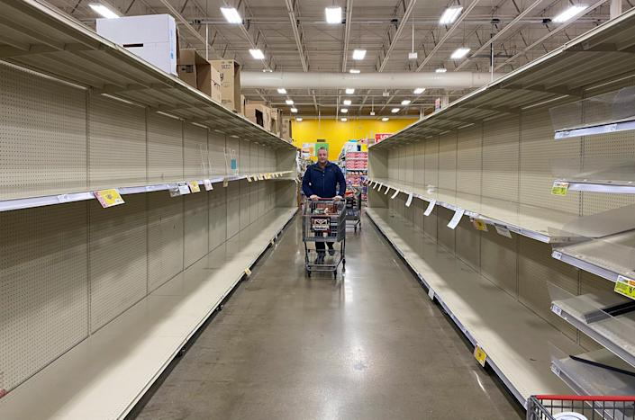 Customers at grocery chain HEB in Austin look for products among increasingly empty shelves as the city responds to concerns of the spread of coronavirus on March 13.
