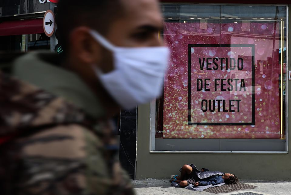 SAO PAULO, BRAZIL - JUNE 29: A man wearing a face mask walks in front of a store while a homeless man sleep on the floor in downtown amidst the coronavirus (COVID-19) pandemic on June 29, 2020 in Sao Paulo, Brazil. Many businesses in the city of Sao Paulo went bankrupt and some commercial spaces are either for sale or for lease during the coronavirus (COVID-19) pandemic. (Photo by Alexandre Schneider/Getty Images)