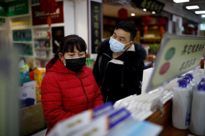 People wearing face masks look for products at a pharmacy as the country is hit by an outbreak of the new coronavirus