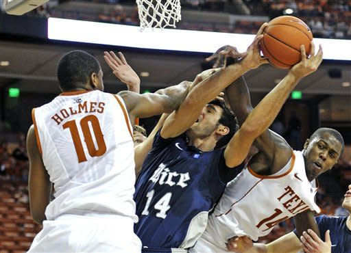 Rice forward Arsalan Kazemi (14) is fouled by Texas forward Jonathan Holmes (10) and J'Covan Brown (14) during the second half of an NCAA college basketball game, Saturday, Dec. 31, 2011, in Austin, Texas. Texas won 73-59. (AP Photo/Michael Thomas)