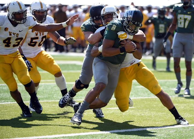 Oregon quarterback Marcus Mariota (8) runs through Wyoming linebacker Mark Nzeocha (21) for a touchdown during the second quarter of an NCAA college football game at Autzen Stadium, Saturday, Sept. 13, 2014, in Eugene, Ore. (AP Photo/Steve Dykes)