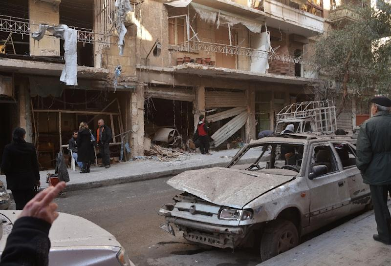 Syrian residents look at the damage following reported rebel shelling in Aleppo's government-controlled neighbourhood of Suleimaniyeh, on February 14, 2016 (AFP Photo/George Ourfalian)