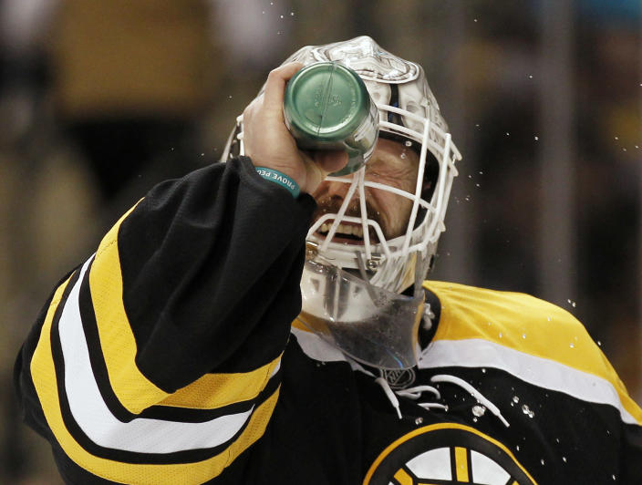 Boston Bruins goalie Tim Thomas sprays water on his face during the first period of their 4-3 loss to the Washington Capitals in Game 5 in a first-round NHL Stanley Cup playoff hockey series in Boston Saturday, April 21, 2012. (AP Photo/Winslow Townson)