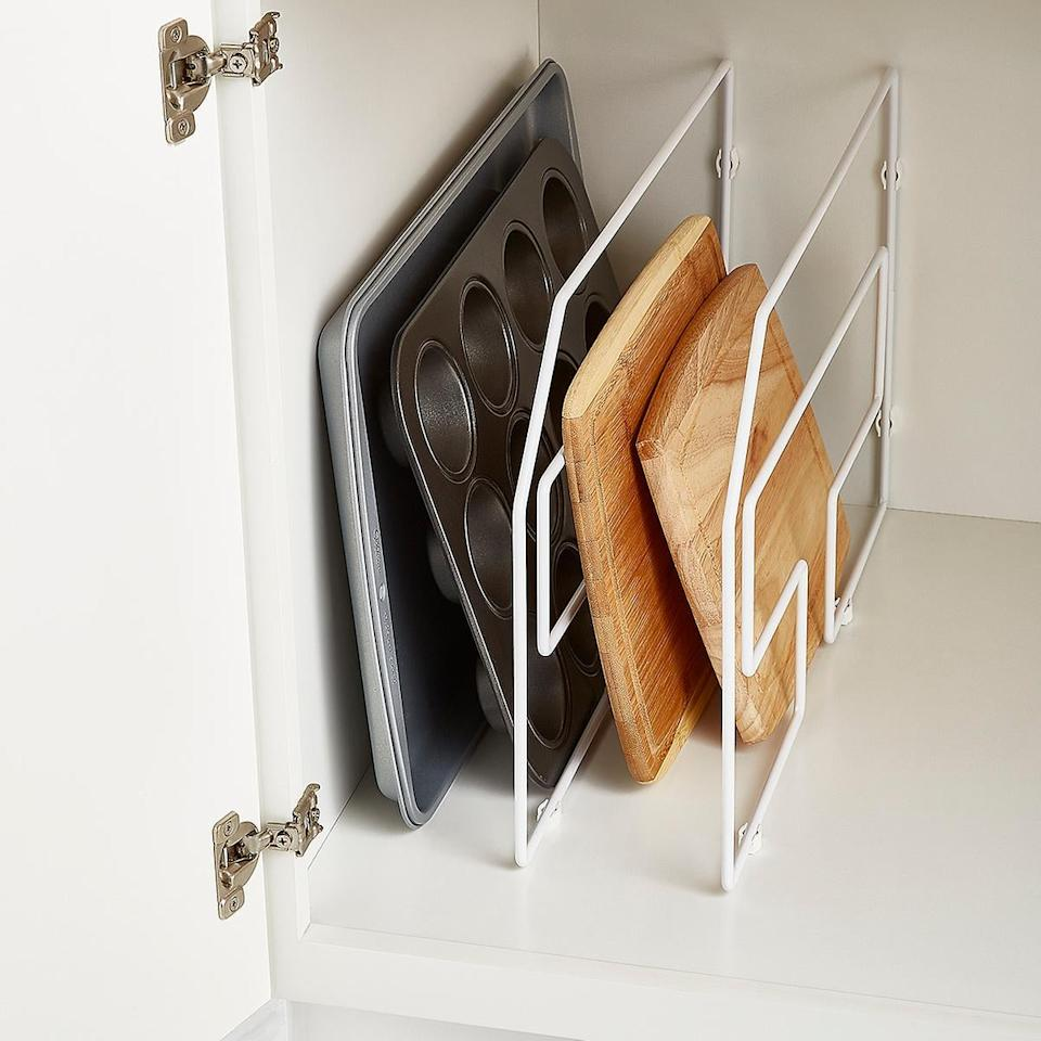 """<p>Your cabinet will suddenly feel so much more spacious with the help of this <a href=""""https://www.popsugar.com/buy/Design-Ideas-12-Tray-Divider-495324?p_name=Design%20Ideas%2012%22%20Tray%20Divider&retailer=containerstore.com&pid=495324&price=15&evar1=casa%3Aus&evar9=46689190&evar98=https%3A%2F%2Fwww.popsugar.com%2Fhome%2Fphoto-gallery%2F46689190%2Fimage%2F46689352%2FDesign-Ideas-12-Tray-Divider&list1=shopping%2Corganization%2Ckitchens%2Chome%20organization&prop13=api&pdata=1"""" rel=""""nofollow"""" data-shoppable-link=""""1"""" target=""""_blank"""" class=""""ga-track"""" data-ga-category=""""Related"""" data-ga-label=""""https://www.containerstore.com/s/kitchen/25/design-ideas-12-tray-divider/1pd?productId=10004540"""" data-ga-action=""""In-Line Links"""">Design Ideas 12"""" Tray Divider</a> ($15).</p>"""