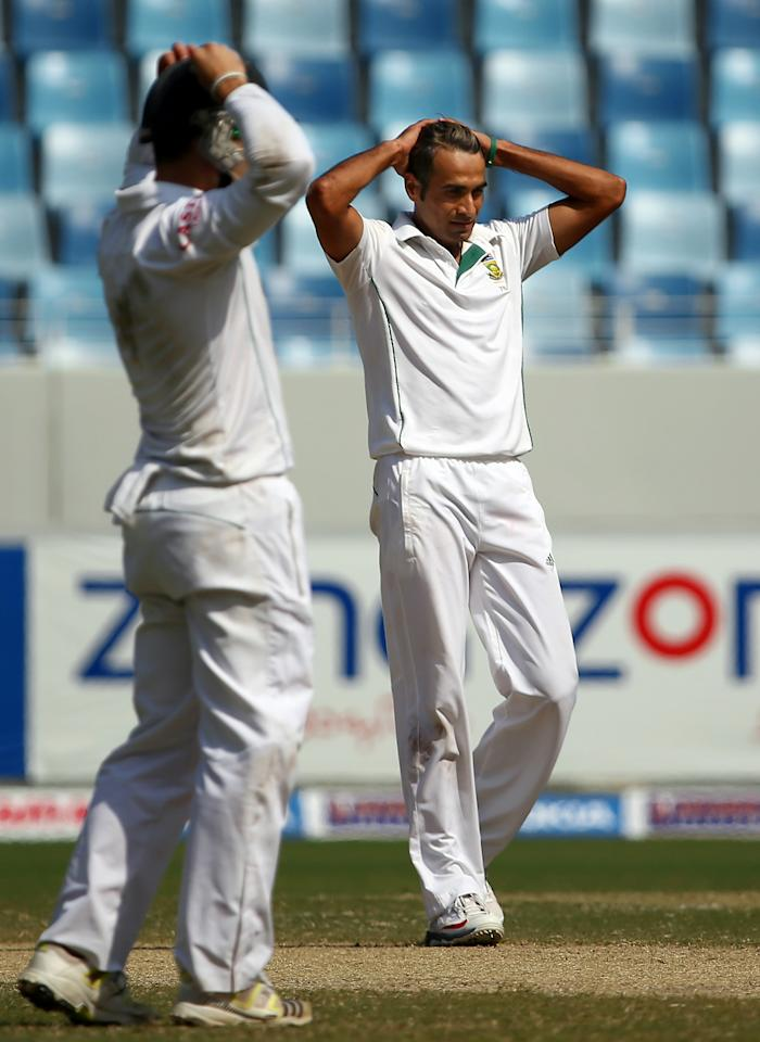 Bowler Imran Tahir (R) of South Africa and a teammate react after playing a shot during the fourth day of the second Test cricket match between Pakistan and South Africa in Dubai on October 26, 2013. AFP PHOTO/MARWAN NAAMANI        (Photo credit should read MARWAN NAAMANI/AFP/Getty Images)