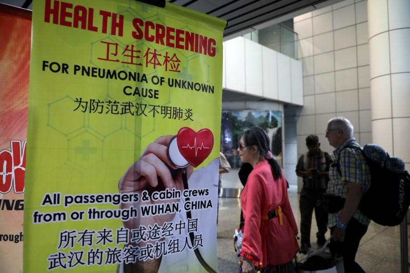 FILE PHOTO: Passengers pass a banner about Wuhan Pneumonia at a thermal screening point in the international arrival terminal of Kuala Lumpur International Airport in Sepang