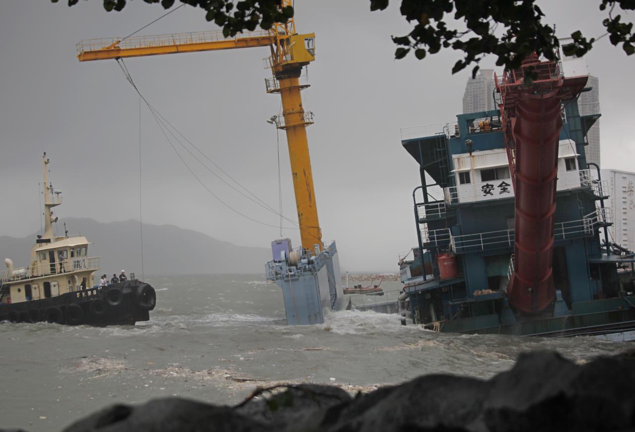 A barge, right, is seen run aground with its moorings slipped off by Typhoon Nesat in Hong Kong Thursday, Sept. 29, 2011. Residents of Hong Kong hunkered down as they rode out a powerful typhoon that brought death and destruction when it tore through the Philippines earlier this week. Hong Kong's stock market suspended trading and shops and businesses shuttered as Typhoon Nesat made its way across the South China Sea from the Philippines, where the storm killed 35 people and that left another 45 missing. (AP Photo/Vincent Yu)