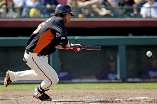San Francisco Giants' Brandon Crawford gets on base with a bunt single against the Los Angeles Dodgers during the fifth inning of a spring training baseball game, Wednesday, March 28, 2012, in Scottsdale, Ariz. (AP Photo/Marcio Jose Sanchez)