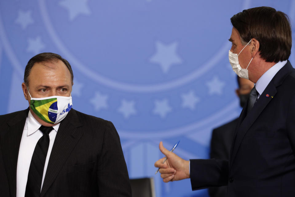Brazil's President Jair Bolsonaro, wearing a mask to curb the spread of COVID-19, talks with Health Minister Gen. Eduardo Pazuelo during a ceremony at the Planalto Presidential Palace, in Brasilia, Brazil, Wednesday, Sept. 16, 2020. After almost four months overseeing the COVID-19 response as interim health minister, Gen. Eduardo Pazuello will finally be made a full minister. (AP Photo/Eraldo Peres)